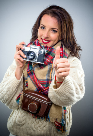 Smiling happy female photographer holding a retro camera with the leather case around her neck giving a thumbs up of approval and success