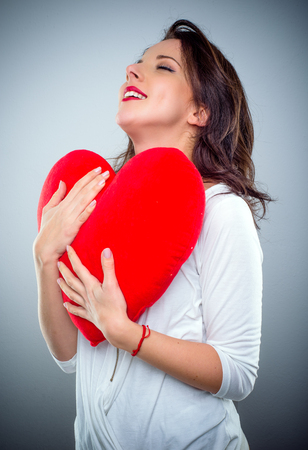 Young woman in love clutching a red heart with a smile of pleasure as she romanticises about her Valentines sweetheart, over grey Stock Photo