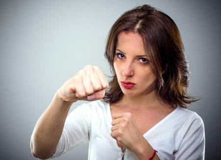 conflicted: Combative young woman punching at the camera with her bare fist and a determined expression, head and shoulders on grey