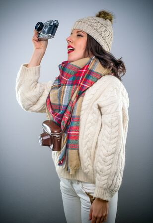 Stylish attractive young woman in winter fashion with a vintage camera holding it up in the air as she squints at it with a look of concentration, side view on grey