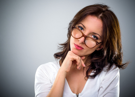woman  glasses: Thoughtful attractive young brunette woman wearing glasses resting her chin on her hands peering over the top of the frames, over grey with copy space