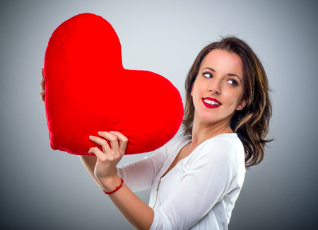 Playful young woman holding a red heart looking back over her shoulder with a happy smile, side view conceptual of a Valentines sweetheart on grey