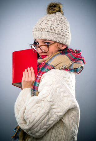Attractive young woman reading a colorful red book in her warm winter outfit holding the book to her face as she glances sideways at the camera with a smile while peering over her glasses