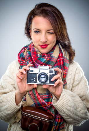 Beautiful young woman winks while taking photo with retro camera Stock Photo