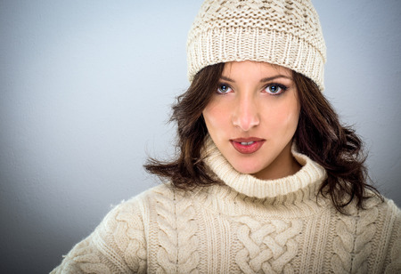 Pretty young woman with shoulder length brown hair in winter woollens wearing a knitted cap and jumper, head and shoulders on grey with copy space