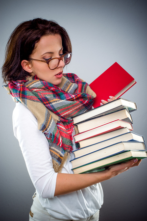 Attractive young female librarian or teacher wearing glasses and a colorful scarf holding a pile of books in her hand checking the title of one with a serious expression