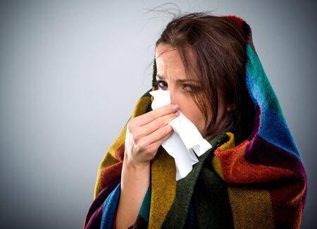 Young woman with a winter cold bundled up warmly on a colorful blanket blowing her nose on a tissue Standard-Bild