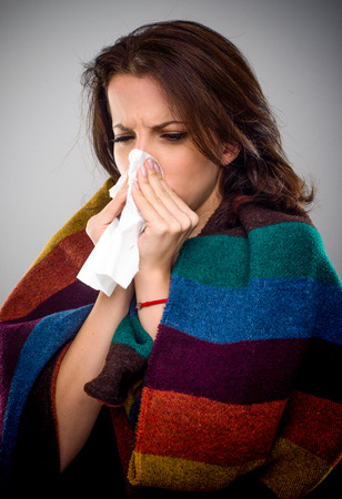 Sick woman with a winter cold huddling down in a warm blanket blowing her nose on a white tissue