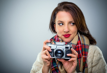 Attractive stylish woman with a retro camera in her hands looking sideways with a smile as she awaits her opportunity to snap a photograph