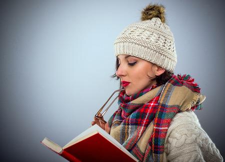 jovenes estudiantes: atractiva joven pensativo en un equipo de moda de invierno lectura de un libro de tapa dura de color rojo colorido con sus gafas en su mano, la cabeza y los hombros vista de perfil Foto de archivo