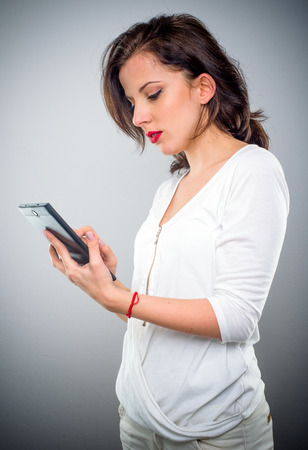 Attractive casual young woman checking her mobile phone for text messages looking at the screen with a serious expression, upper body side view on grey