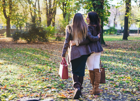 Two happy trendy young women strolling arm in arm through an autumn or fall park carrying fashionable handbags, rear view walking away from camera