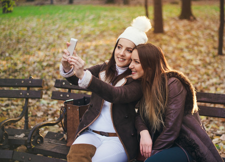 Two attractive trendy girlfriends taking a selfie posing close together on a bench in an autumn park smiling happily for the camera Standard-Bild