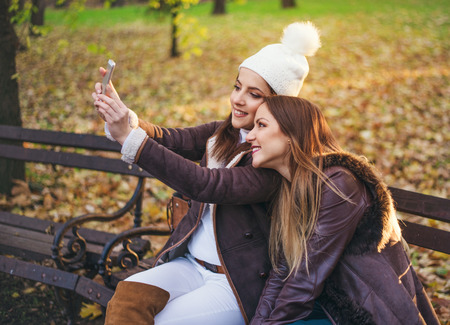 Two stylish young women taking a selfie on a mobile phone as they relax together on a bench in an autumn or fall park