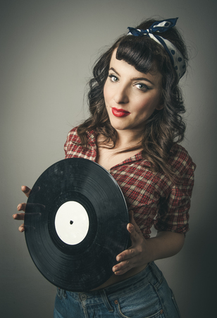 Cute retro pin up girl with a vintage hairstyle in ringlets and bobs and bandanna in her hair standing holding a vinyl record in her hands smiling at the camera in a beauty portrait Standard-Bild