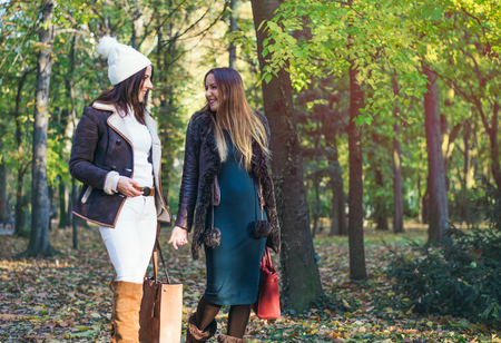Two elegant young woman walking through a park in autumn chatting and laughing as they walk through woodland, close up with copy space