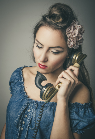 Head and shoulders portrait of glamorous woman in vintage clothes using retro telephone