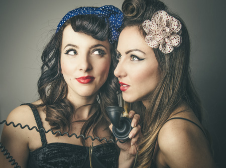 Two fashionable young female friends in vintage clothes sharing retro telephone Stock Photo - 68262418