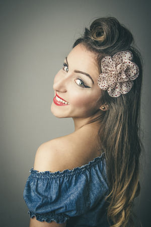 Head and shoulders portrait of smiling fashionable young woman in vintage clothes looking over shoulder, studio background