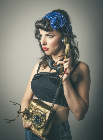 Half body portrait of thoughtful fashionable young woman in vintage clothes with retro telephone, studio background Stock Photo