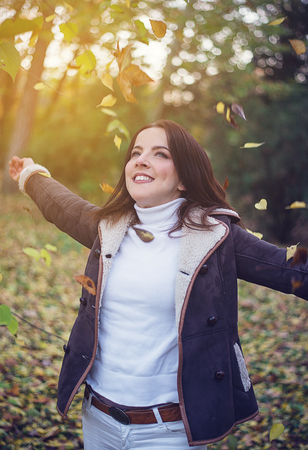 Happy young woman playing with autumn leaves in colorful woodland tossing them in the air with a joyful smile in the glow of the sun Stock Photo