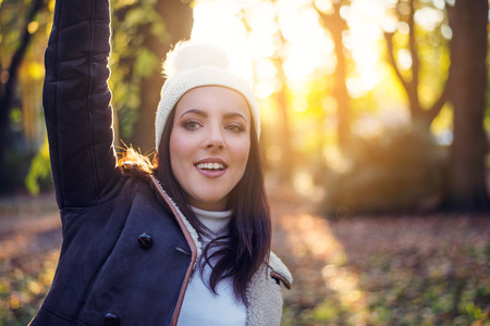 Happy pretty young woman in an autumn forest standing facing the camera waving with a smile against the bright warm glow of the evening sun Standard-Bild