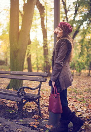 Stylish young woman in an autumn park standing alongside a rustic wrought iron and wooden bench leaning on a pole waiting for somebody Standard-Bild
