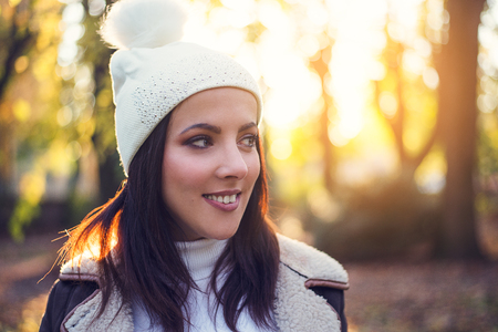 Attractive young woman wearing a white knitted hat with pompom enjoying an autumn evening outdoors in a wooded park looking to the side with a smile against the warm glow of the setting sun Standard-Bild