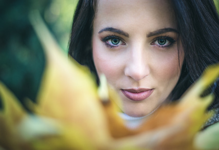 Pretty serene young woman looking over colorful yellow autumn leaves at the camera with a quiet gentle smile, close up of her face