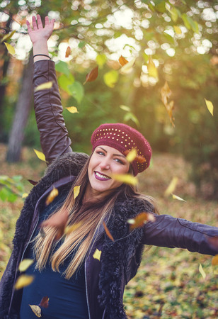 Pretty young woman celebrating the fall season outdoors in a wooded park throwing colorful autumn leaves into the air with outstretched arms and a happy smile