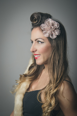 Side portrait of smiling fashionable woman with fancy hairstyle and bow in hair, studio background