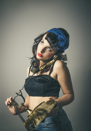 Three quarter body portrait of fashionable young woman in vintage clothes with sexy expression, studio background