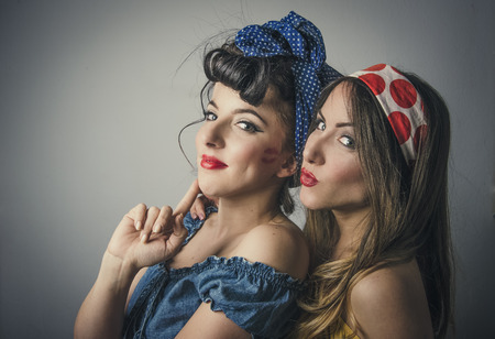 Portrait of two sexy young women in retro clothing with pouting lips, studio background