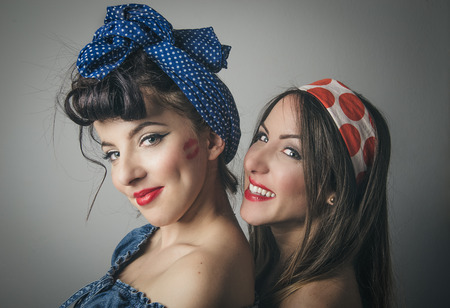 Portrait of two young female friends in retro clothing with hair bands looking over shoulder Stock Photo