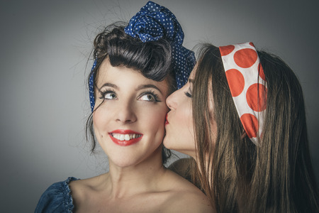 Portrait of two happy young women in retro clothes, one kissing the cheek of her friend, studio background