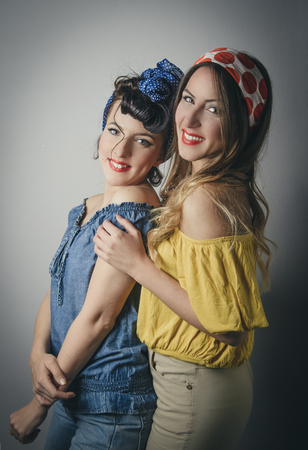 Side three quarter body portrait of two pretty smiling young women in retro clothing looking over shoulder
