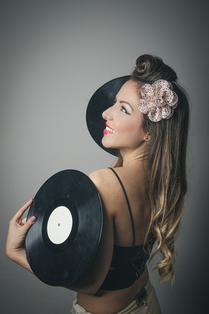 Side view of smiling beautiful young woman with two vinyl records, studio background Standard-Bild