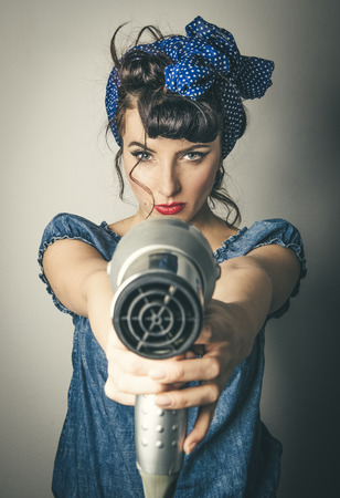Half body portrait of young woman in vintage clothes pointing hairdryer