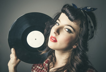 Attractive young woman in 60s style vintage clothes holding vinyl record by head Stock Photo