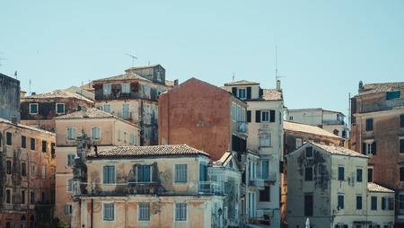 Cascade of peeling old mediterranean houses against clear blue sky - Corfu, Greece Stock Photo