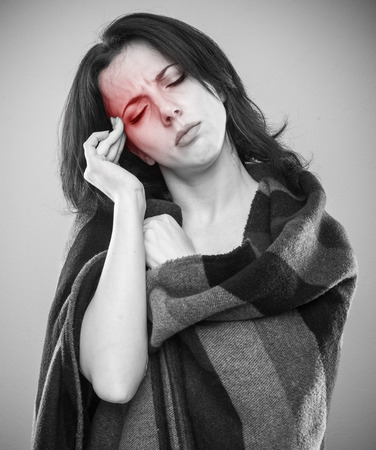 Young woman wrapped in blanket with her fingers to her temple as if experiencing headache, grayscale portrait with red pain area