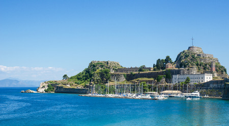 Scenery view of blue sea and boats moored near ancient mediterranean castle on Corfu island, Greece