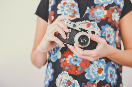 Close-up of incognito woman in sleeveless dress with flowers pattern holding vintage photo camera in front of her adjusting lens