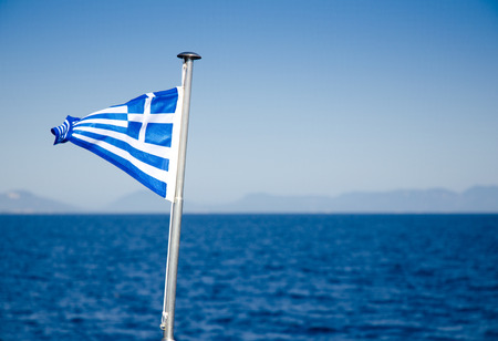 Close-up of Greece flag waving on metal flagpole over vessel with blue sea, sky and mountainous horizon in background