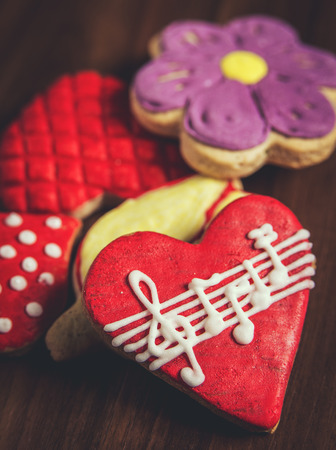 Close-up of several sugar cookies with royal icing glaze of different colors, one red heart-shaped with musical notes in foreground Stock Photo