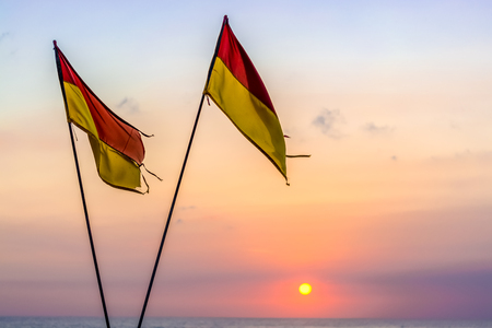 Red & yellow beach safety flags that are crossed signalling that the beach is no longer being patrolled by life guards. Stock Photo