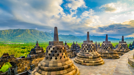 Large carved stone bells at the apex of the worlds largest 9th century Buddhist temple. The temple is also listed as a world hertiage site. In the background is mountains covered lush green foliage.