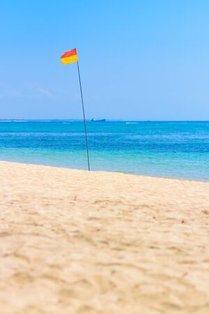signifies: A red and yellow flag pole at he beach i nBali signifies that that area is patrolled by lifeguards.