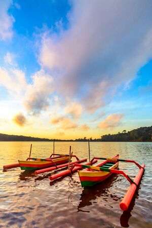 Traditional Indonesia fishing outrigger canoes called Jakung  on the lake at sunrise tied up to a wharf.