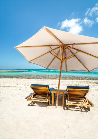 perfect waves: A large Beach Umbrella with lounge chairs on a beautiful beach in Bali.